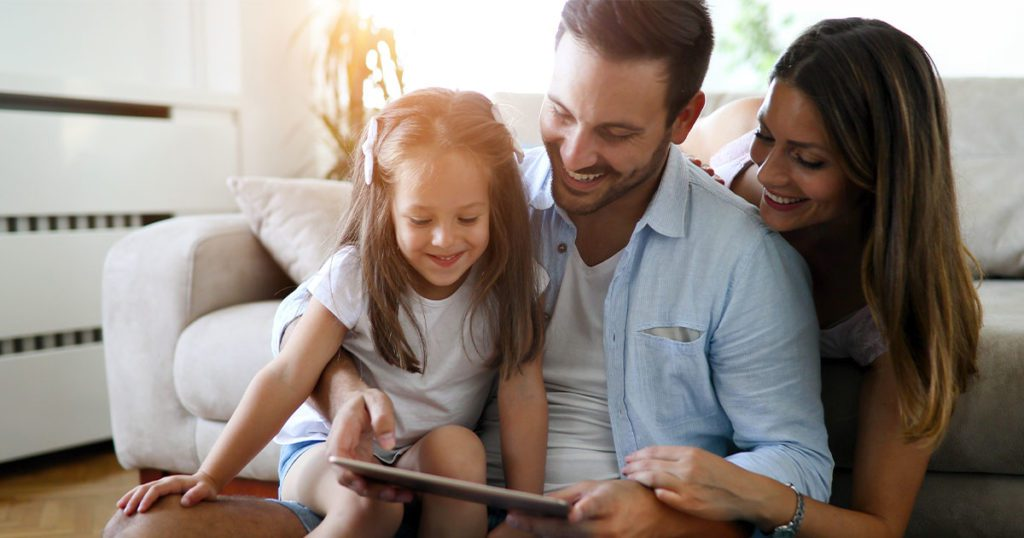 Small family looking at tablet.